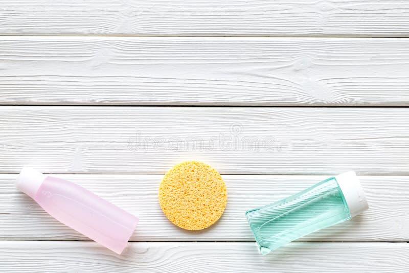 Cosmetici di cura di pelle con tonico facciale, acqua micelia e la spugna sul modello di legno bianco di vista superiore del fond fotografia stock