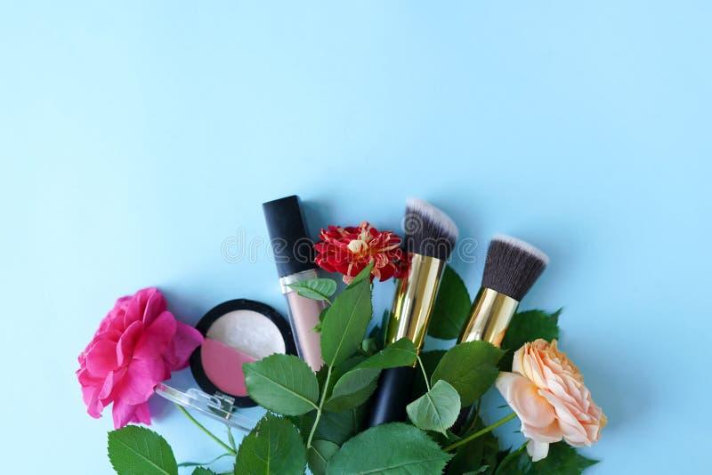 Cosmetici di trucco con i fiori su fondo blu, spazio della copia bellezza, blogging fotografia stock libera da diritti