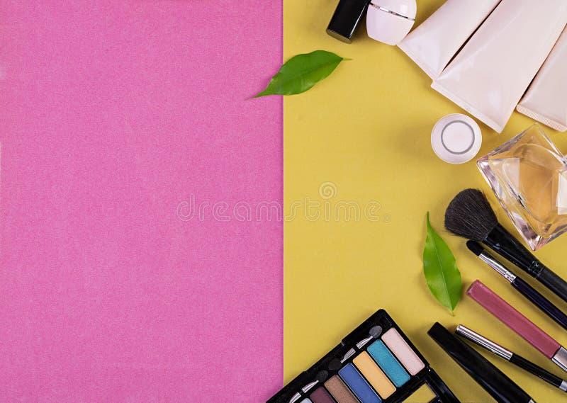 Cosmetici di trucco su fondo rosa-giallo Vista superiore Copi lo spazio fotografia stock libera da diritti