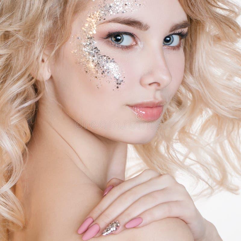 Cosmetici e manicure Il ritratto delle donne di bellezza di giovane donna bionda riccia con il manicure pastello e l'arte perfett fotografia stock