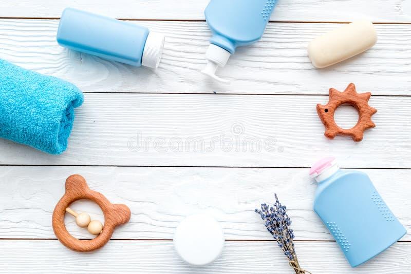 Cosmetici ipoallergenici naturali del ` s dei bambini Bottiglie, asciugamano e giocattoli sul copyspace di legno bianco di vista  immagini stock libere da diritti