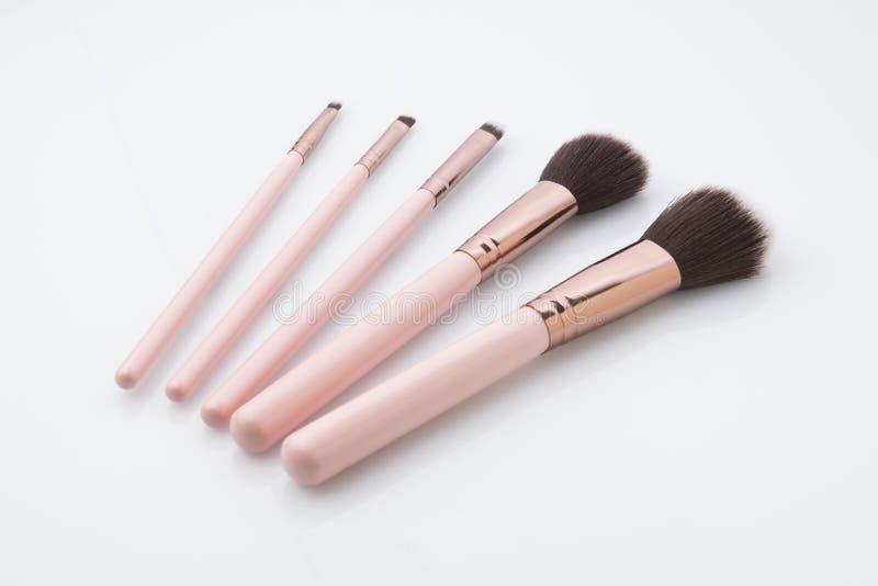 Cosmetici: Metta di compongono le spazzole sparate in studio sopra fondo bianco fotografie stock