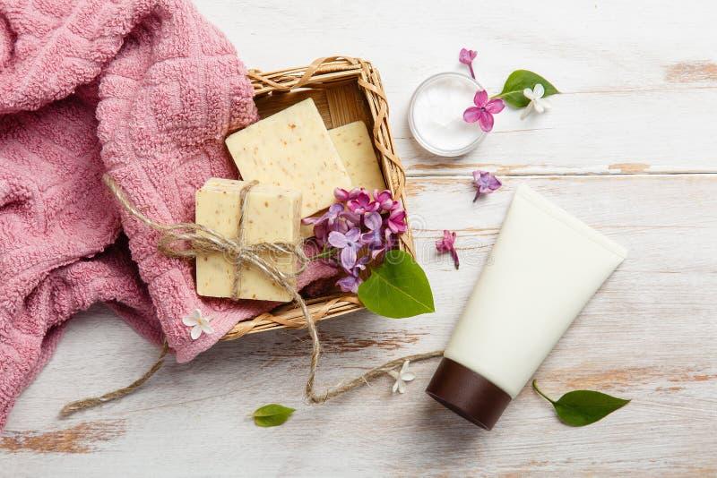 Cosmetici naturali con i fiori lilla Metta dei rotoli dell'asciugamano e della crema fotografia stock