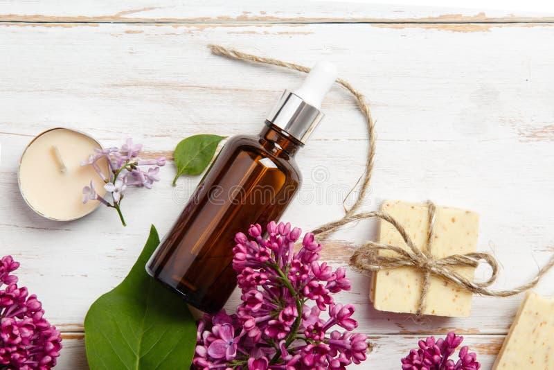 Cosmetici naturali con i fiori lilla Siero, sapone e crema Prodotti di cura del fronte Prepari al bagno fotografia stock libera da diritti