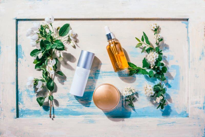 Cosmetici organici naturali: siero, crema, maschera su fondo di legno con i fiori Concetto della stazione termale fotografie stock