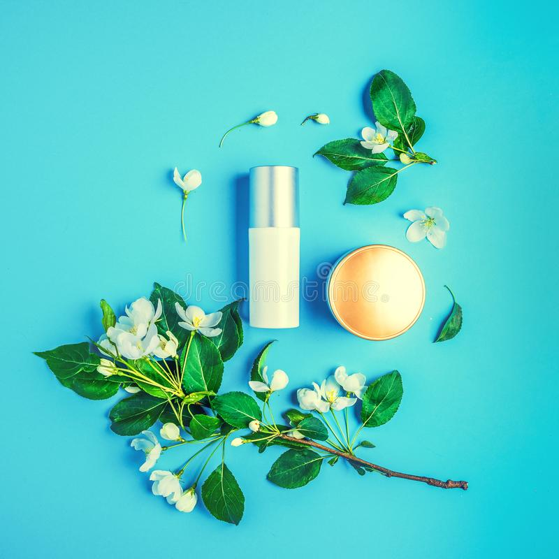Cosmetici organici naturali su fondo blu nel telaio dei fiori, di melo sbocciante fotografie stock libere da diritti
