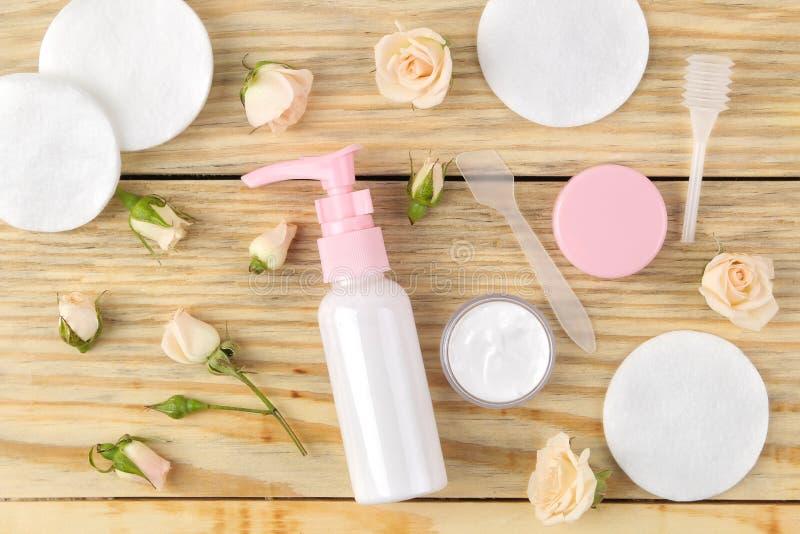 Cosmetici per il fronte ed il corpo Crema in bottiglie rosa con le rose fresche su un fondo di legno naturale screma e lozione St fotografia stock