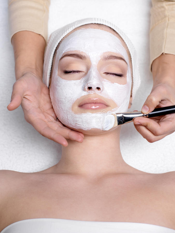 Cosmetician apllying mask on face of woman stock images