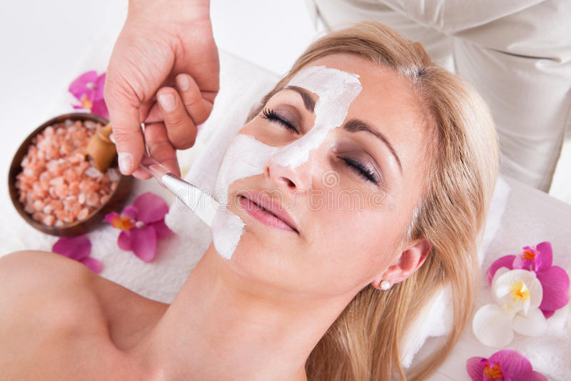 Cosmetician applying facial mask on face of woman. Cosmetician Applying Facial Mask To The Face Of Young Beautiful Woman In Spa Salon stock image