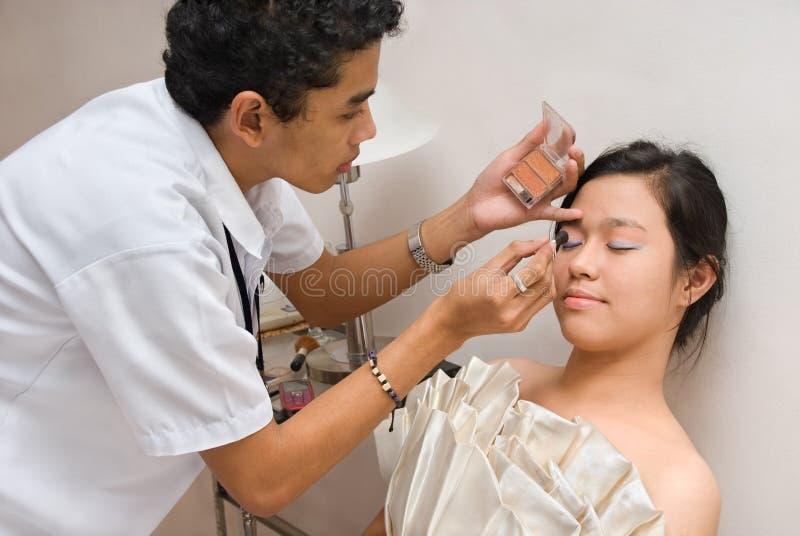 Cosmetician brushing face of Asian girl stock image