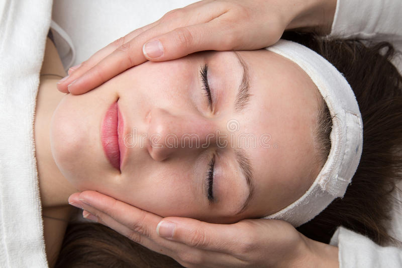 Cosmetician giving customer face massage. Cosmetician giving client a facial massage royalty free stock image