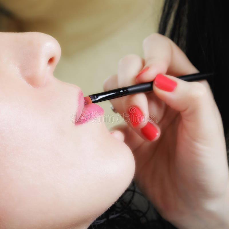 Cosmetician som applicerar läppstift arkivfoton