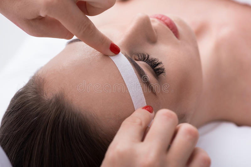 Cosmetician undergoing waxing procedure for human brow. Close-up of beautician hands applying wax paper stick near female eyebrow stock images