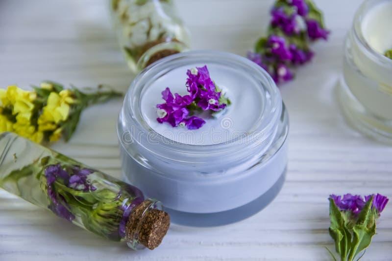 Cosmetico crema, pianta dei fiori selvaggi, annata organica dell'essenza dell'idratante di freschezza su un fondo di legno fotografie stock libere da diritti