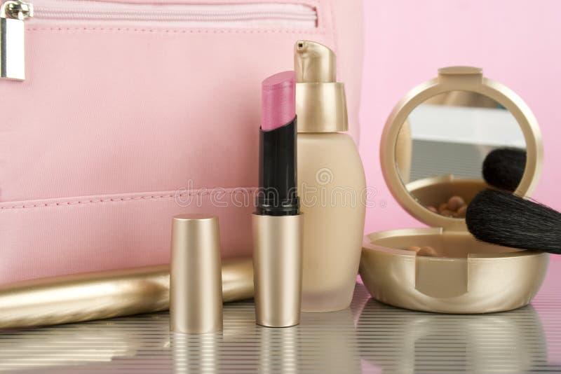 Cosmetics. On the table. Basic colors pink and gold. Powder, skin cream, lipstick, handbag, vanity case, brush, eyeliner royalty free stock photography