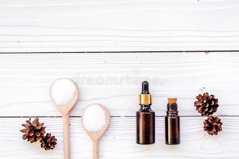 Cosmetics and aromatherapy concept. Pine spa salt, oil and pinecones on white wooden background top view copyspace. Cosmetics and aromatherapy concept. Pine spa royalty free stock image