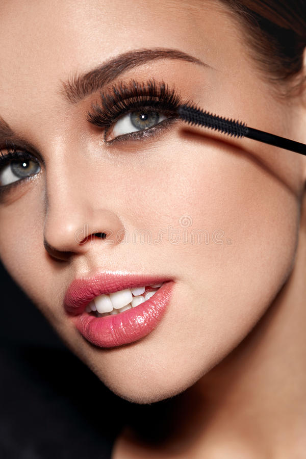 Cosmetics. Beautiful Woman With Perfect Makeup Applying Mascara royalty free stock images