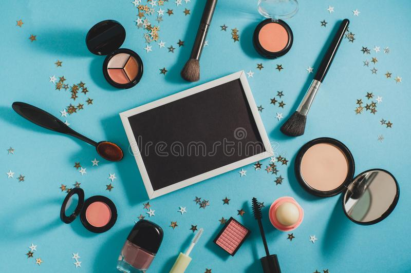 Cosmetics - Beauty blog concept. Cosmetics - powder, blush, brushes, mascara, shadows on a blue background. In the center is a black board for text. Beauty blog stock images