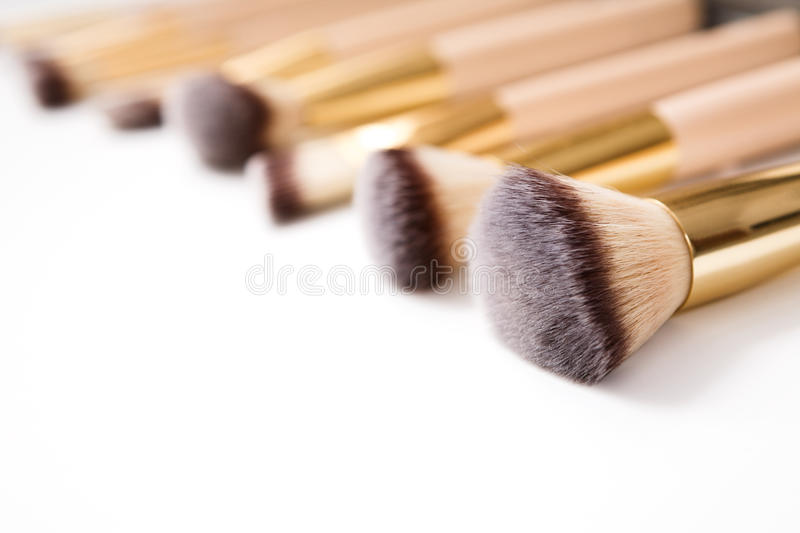 Cosmetics, beauty, make-up brushes set in row, shallow depth stock photography