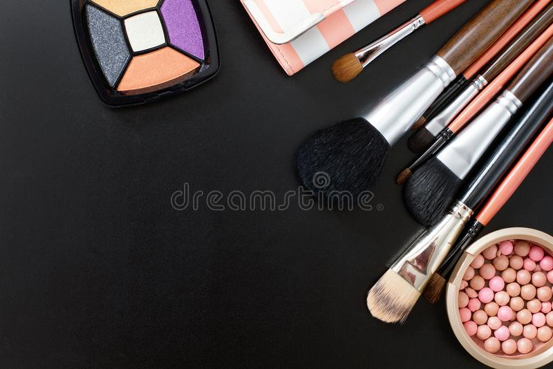 Make up tools. Cosmetics on black background and make up tools. Top view and mock up. Copy space. royalty free stock photography