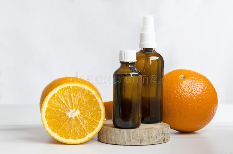 Cosmetics bottles and fresh oranges,wooden board against white wall.Concept of spa treatments. Aroma therapy at spa salon.Oranges and orange oil for healthcare royalty free stock photos