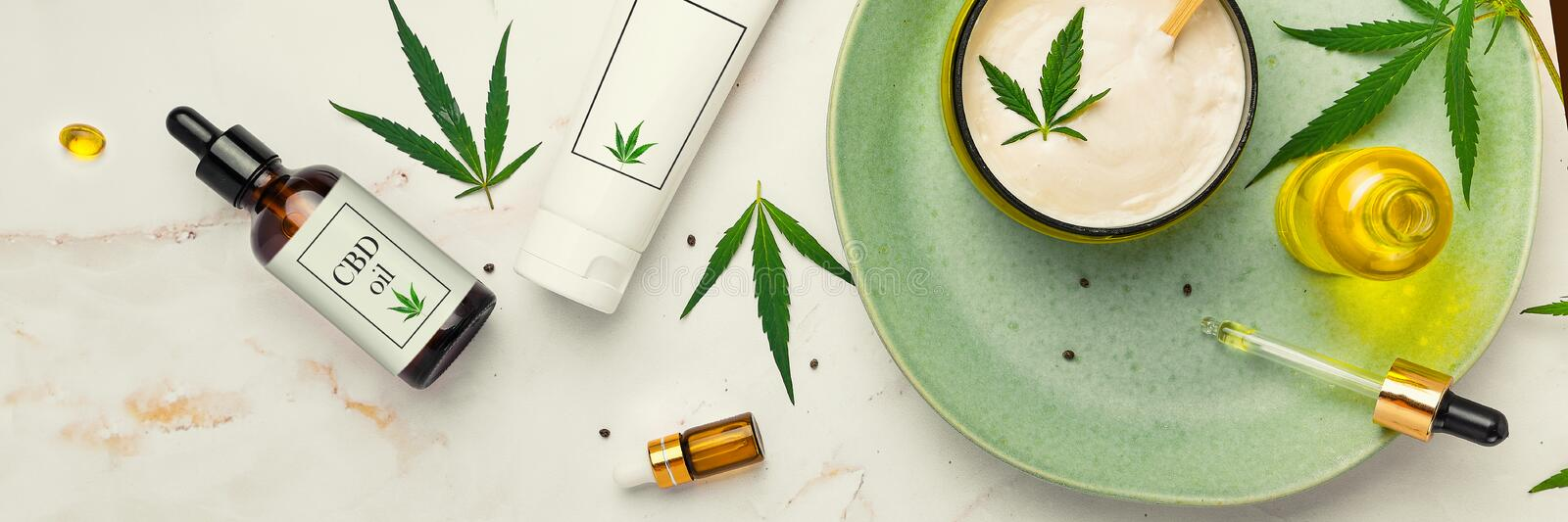 Cosmetics with cannabis oil on a turquoise plate on a light marble background. Concept of luxury skin care. Banner. Cosmetics with cannabis oil on a turquoise stock photography