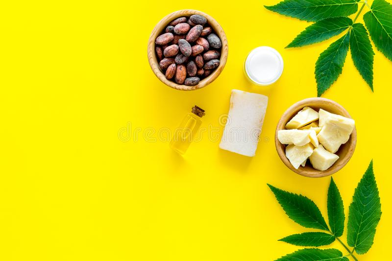Cosmetics with cocoa butter for skin care. Cocoa beans and cocoa butter in bowl, soap, cream, oil or lotion in small stock photo
