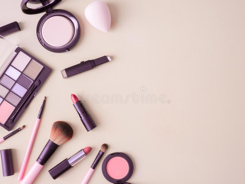Cosmetics concept with lipstick, makeup products, Eyeshadow Palette, powder on cream color table background. royalty free stock images