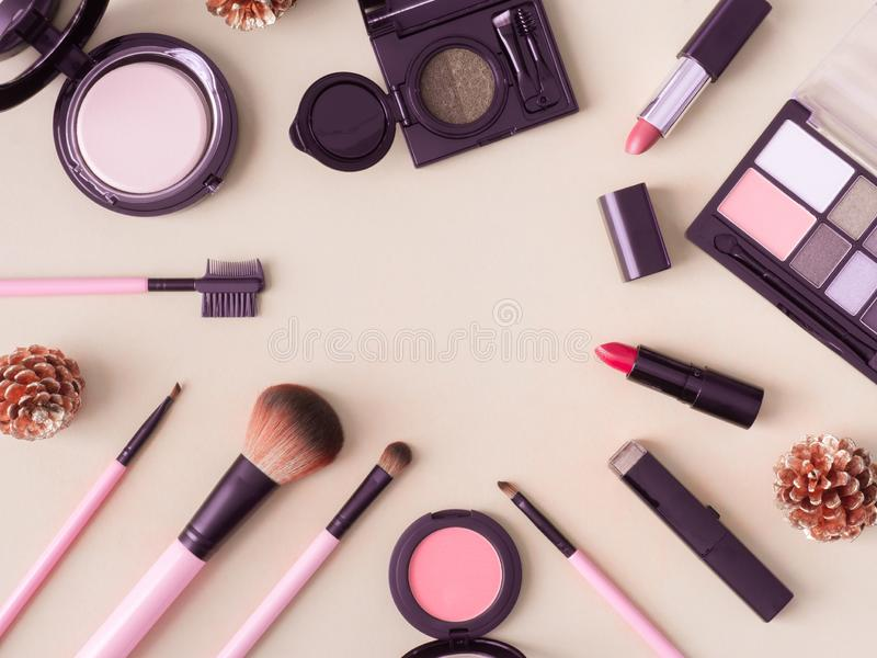 Cosmetics concept with lipstick, makeup products, Eyeshadow Palette, powder on cream color table background. stock image