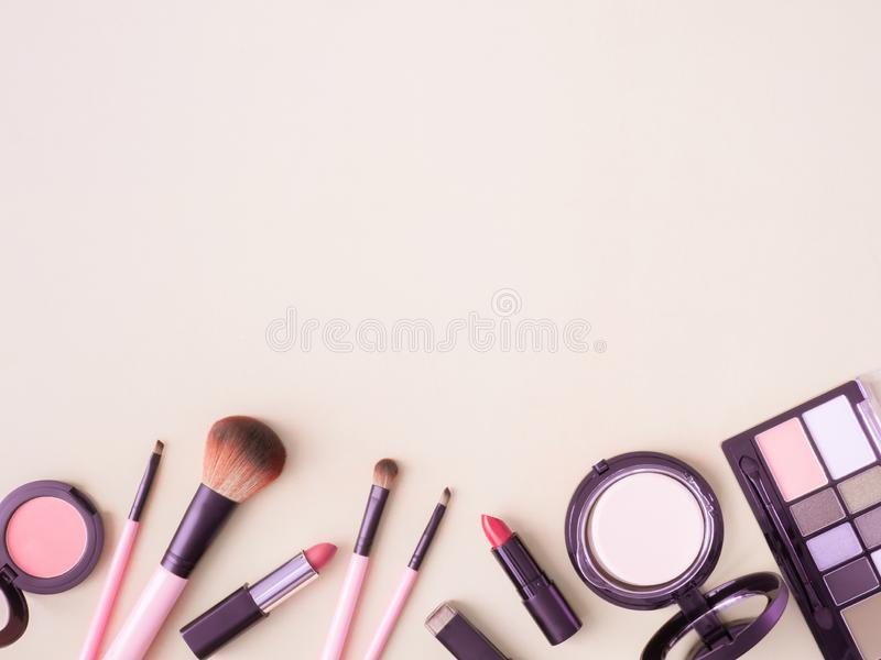 Cosmetics concept with lipstick, makeup products, Eyeshadow Palette, powder on cream color table background. stock photos