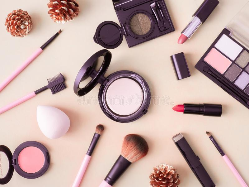 Cosmetics concept with lipstick, makeup products, Eyeshadow Palette, powder on cream color table background. Top view of cosmetics concept with lipstick, makeup royalty free stock photography