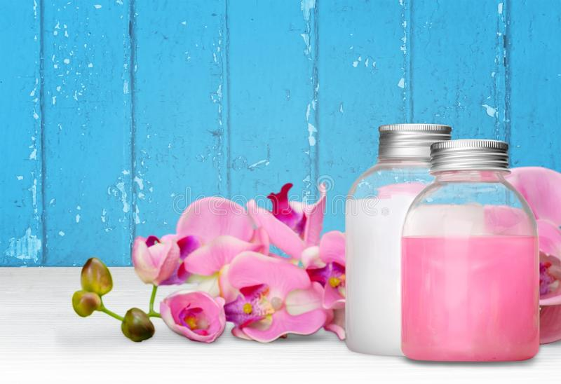 Cosmetics. Shampoo spa treatment orchid flower bottle aromatherapy oil royalty free stock images