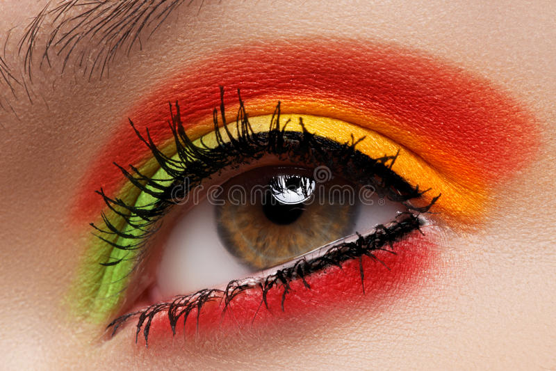 Cosmetics, eyeshadows. Macro fashion eye make-up. Cosmetics and beauty care. Macro close-up of beautiful green female eye with bright fashion make-up. Rainbow royalty free stock images
