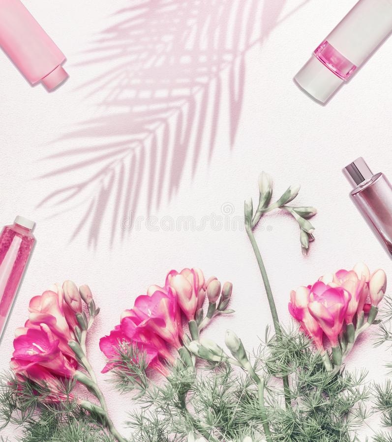 Cosmetics flat lay background with flowers and palm leaves shadow on light background, top view with copy space. Pastel color. stock image