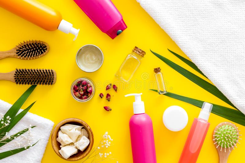 Cosmetics for hair care with jojoba, argan or coconut oil and shampoo in bottle on yellow background top view pattern. Homemade spa. Cosmetics for hair care with royalty free stock image
