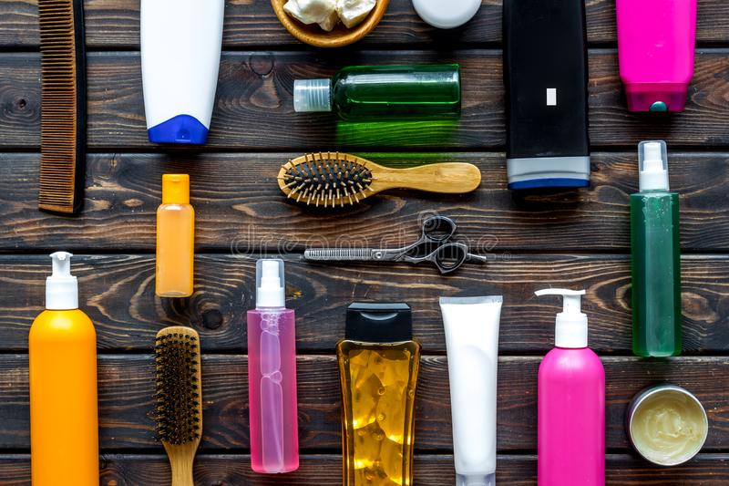 Cosmetics for hair with oil, scissors, comb, conditioner and shampoo in bottle on wooden background top view pattern. Homemade spa. Cosmetics for hair care with stock image