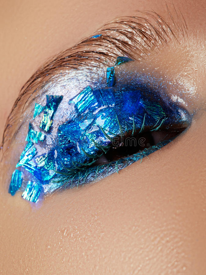 Cosmetics and make-up. Closeup macro shot of fashion sparcle visage. Closeup portrait of beautiful young woman with blue foil on stock photos