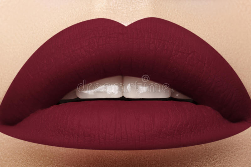 Cosmetics, makeup. Bright lipstick on lips. Closeup of beautiful female mouth with dark red lip makeup. Part of face. Cosmetics, makeup and trends. Bright lip royalty free stock image