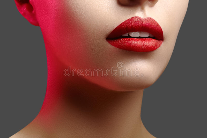 Cosmetics, makeup. Bright lipstick on lips. Closeup of beautiful female mouth with red lip makeup. Clean skin model royalty free stock photography
