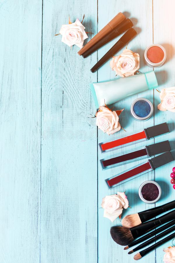 Cosmetics and makeup brushes on vintage blue wooden background royalty free stock photography