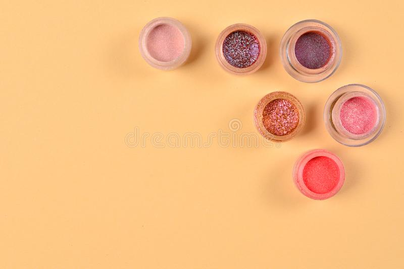 Cosmetics. Makeup. Jars with  crumbly bright shadows, glitter. Pink,peach, golden colors on beige background. Closeup. Space for. Text or design. Top view stock images