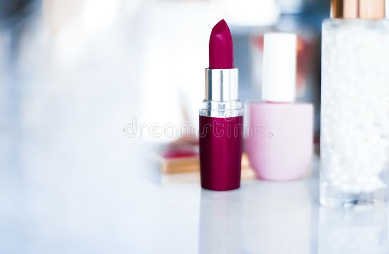 Cosmetics, makeup products on dressing vanity table, lipstick, foundation base, nailpolish and eyeshadows for luxury beauty and stock photography