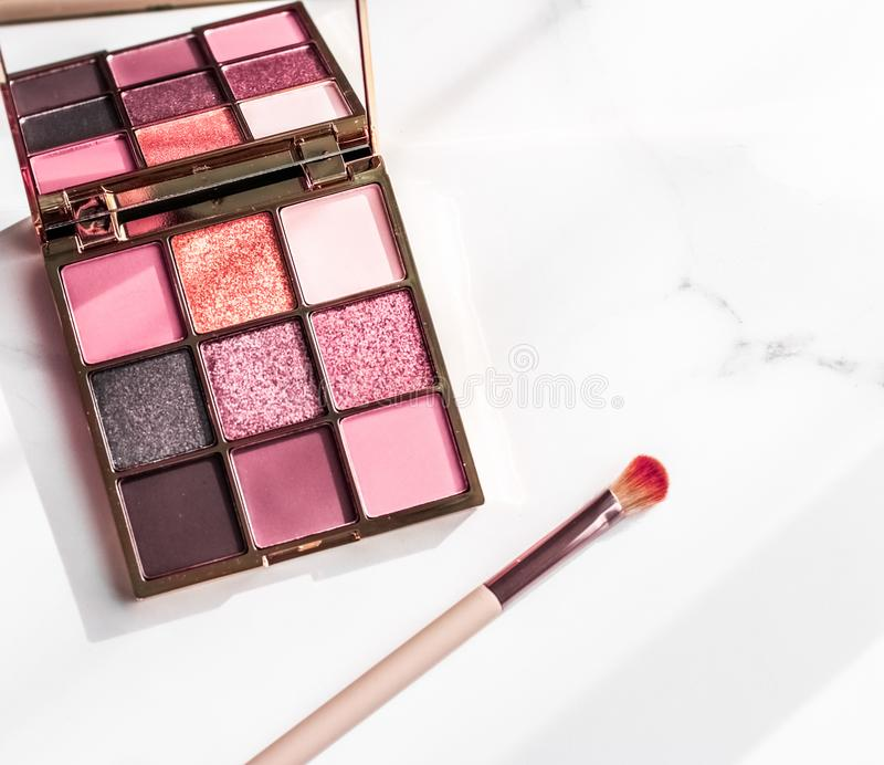 Cosmetics, makeup products set on marble vanity table, lipstick, eyeshadows and make-up brush for luxury beauty and fashion brand stock photo