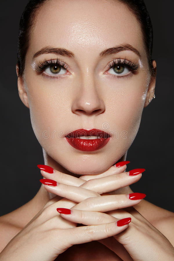 Cosmetics, manicure on nails with bright red polish. Dark red lips make-up and nail color. Luxury woman style vamp. Cosmetics, manicure on nails with bright red stock photo