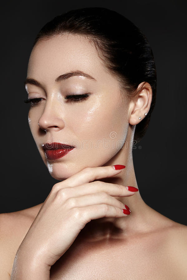 Cosmetics, manicure on nails with bright red polish. Dark red lips make-up and nail color. Luxury woman style vamp. Cosmetics, manicure on nails with bright red royalty free stock photos
