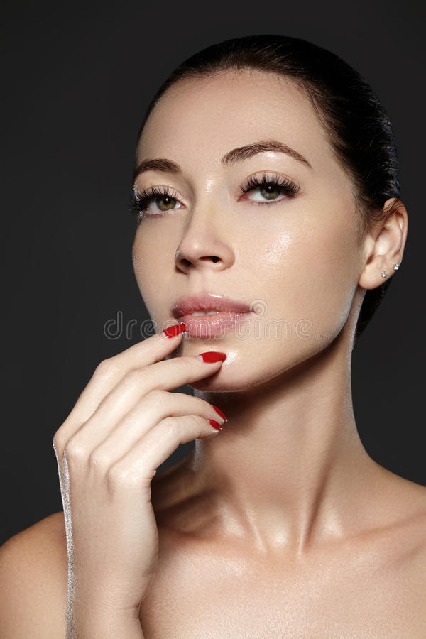 Cosmetics, manicure on nails with bright red polish. Dark red lips make-up and nail color. Luxury woman style vamp. Cosmetics, manicure on nails with bright red stock photography