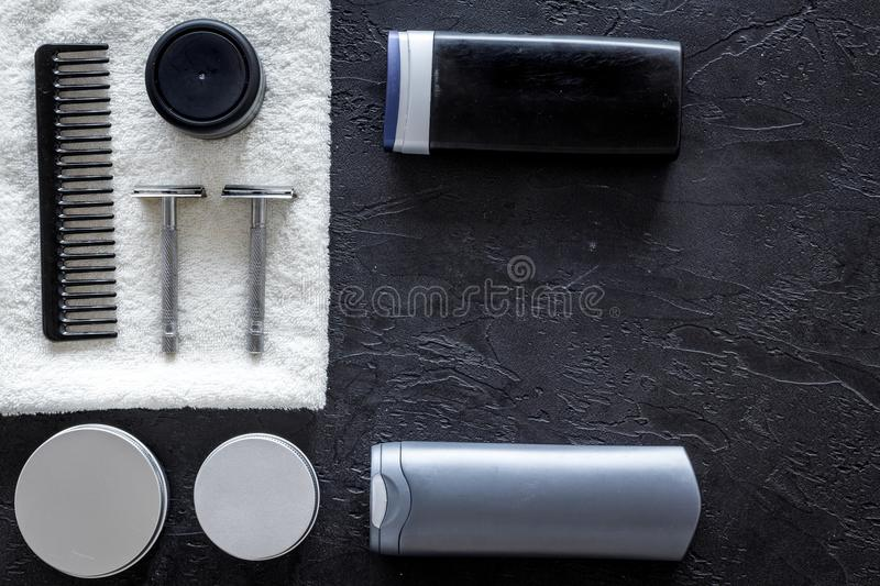 Men`s cosmetics for hair care and shaving. Shampoo, gel, razor, wax on black background top view copyspace. Cosmetics for men on black background top view stock photos