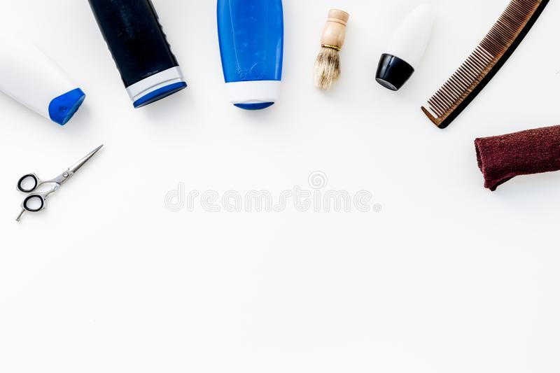 Cosmetics for men`s hair. Bottles with shampoo and gel, tools for brushing, sciccors on white background top view copy stock photo