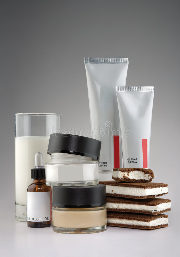 Cosmetics, milk and ice cream. A glass of milk, ice cream sandwiches, tubes, bottle and jars of medical cosmetics stock images