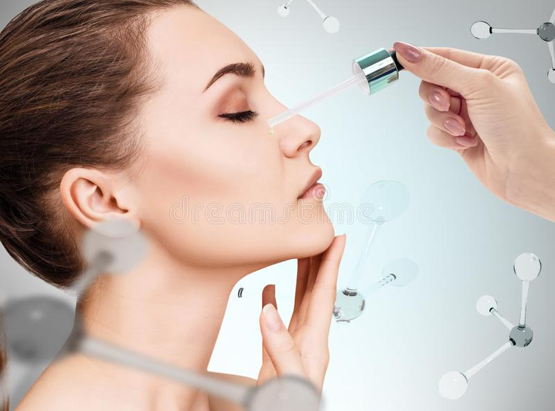 Cosmetics oil on face among the molecules royalty free stock photos